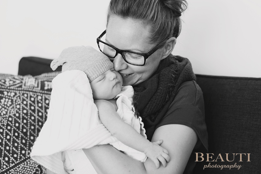 family lifestyle photographer one month old baby girl and mother cuddles sweet moments photo
