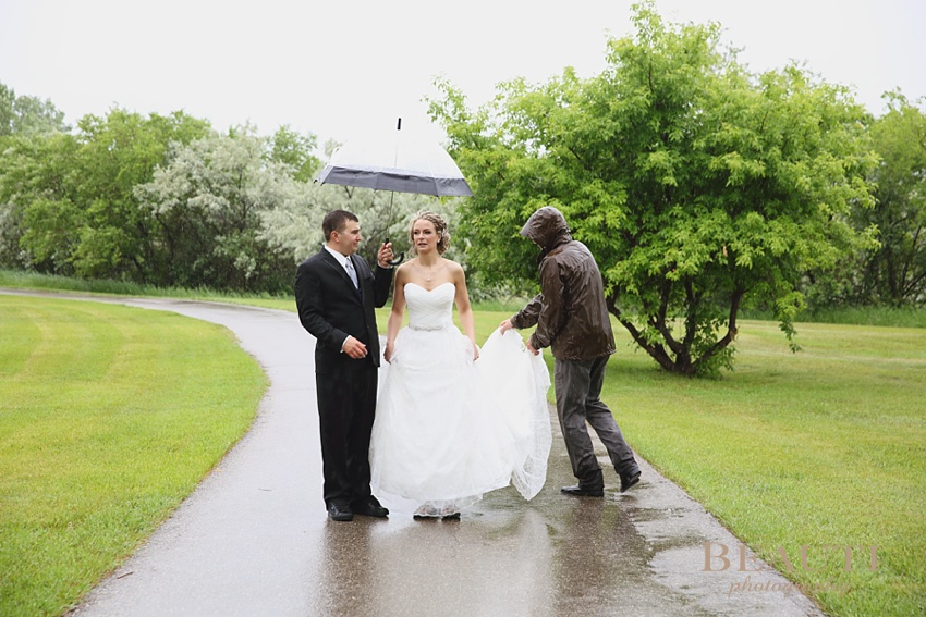 Estevan Saskatchewan wedding photographer outdoor rainy wedding day bride and groom umbrella portraits wedding assistant photo