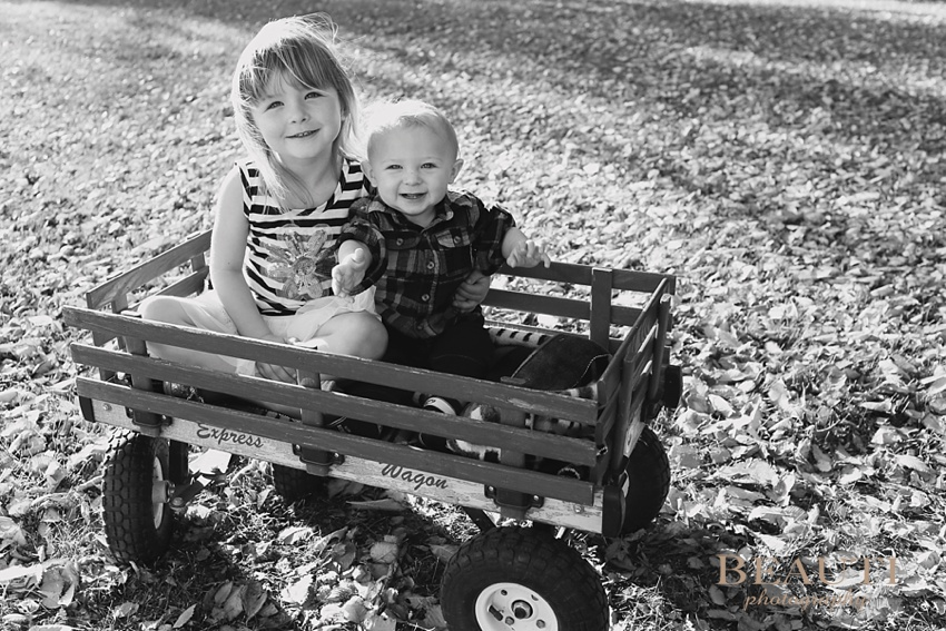 family lifestyle portrait photographer Weyburn outdoor family photography kids in red wagon beautiful fall leaves photo