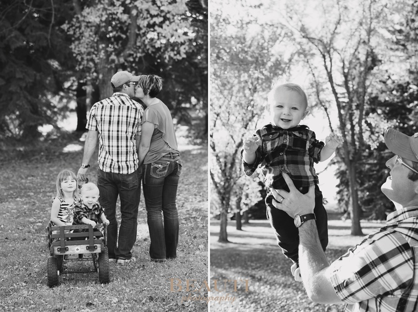 family lifestyle portrait photographer Weyburn outdoor family photography kissing parents pulling kids in red wagon beautiful fall coloured leaves photo