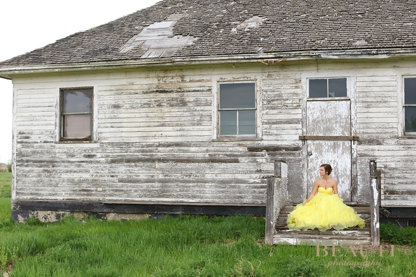 Weyburn graduation 2015 WCS Grad Tribune area portrait photographer Tribune Saskatchewan graduation portraits yellow gown sitting on steps outdoor photo