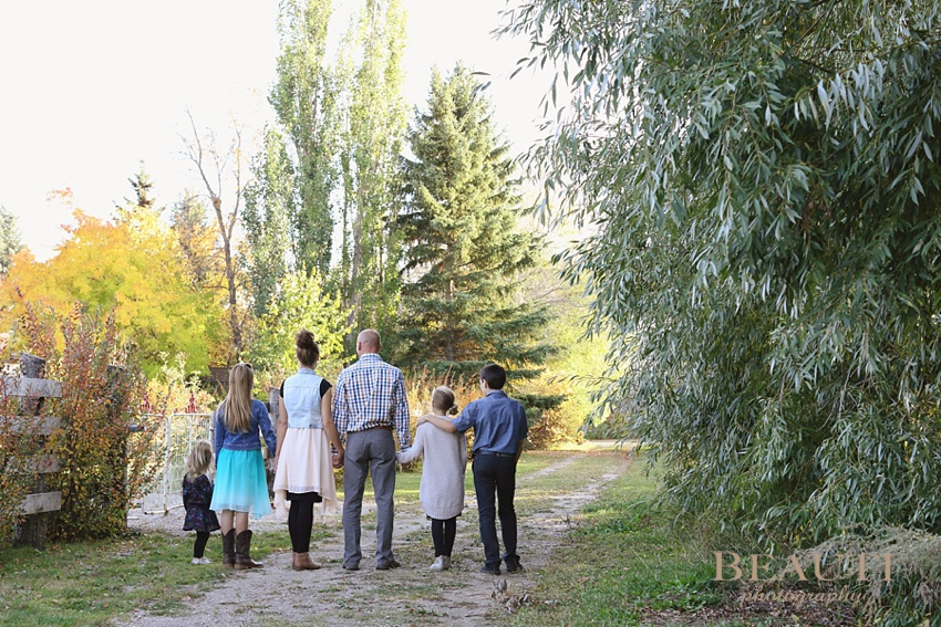 Saskatchewan family lifestyle portrait photographer Windthorst family outdoor portrait photography fall coloured leaves beautiful family moments family holding hands photo