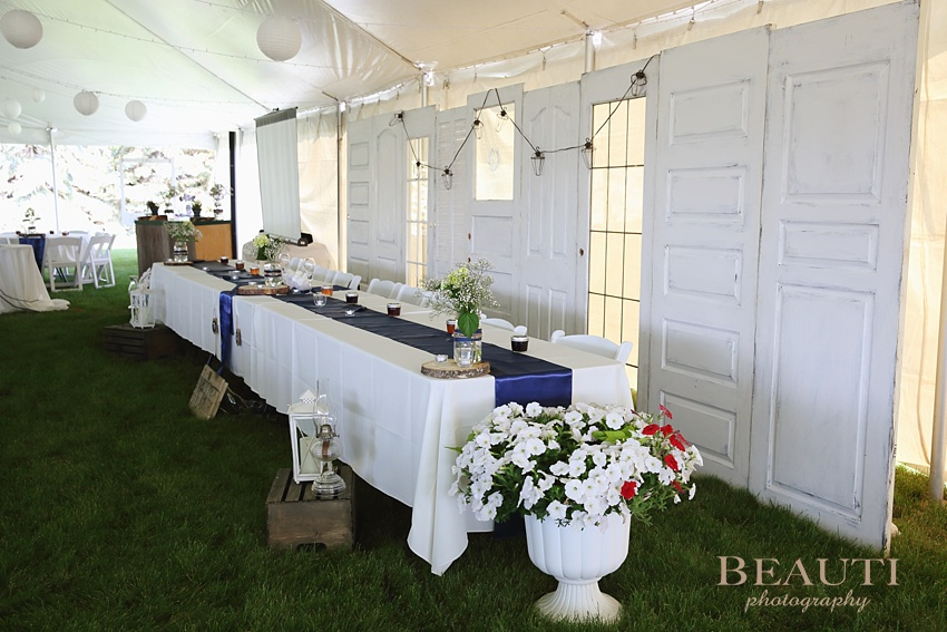 Weyburn wedding reception photography Saskatchewan wedding photographer BEAUTI photography farm summer wedding reception outdoor celebration reception details head table old doors backdrop photo
